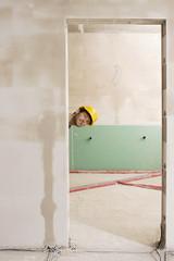 Bauarbeiter späht durch Tür