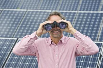 Deutschland, München, Erwachsene schauen durch Fernglas, Solaranlage