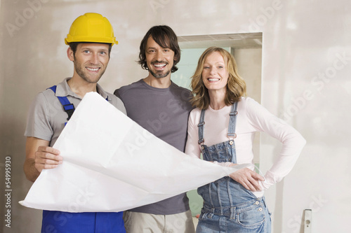 Junges Paar und Bauarbeiter, Blick in den Bauplan