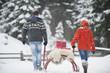 Österreich, Land Salzburg, Flachau, Junger Mann und Frau, die Weihnachtspakete auf Schlitten im Schnee