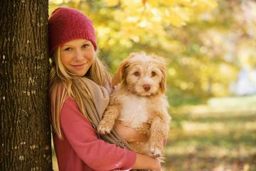 Österreich, Teenager-Mädchen mit Hund neben Baum