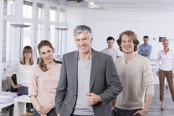Deutschland, Bayern, München, erwachsener Mann mit Kollegen im Büro