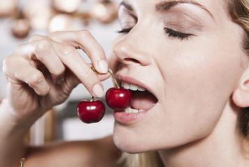 Italien, Toskana, Magliano, Nahaufnahme der jungen Frau, isst Kirschen