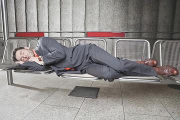 Deutschland, Bayern, München, Geschäftsmann bei der U-Bahn-Station auf der Bank schlafend