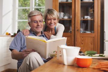 Deutschland, Kratzeburg, älteres Paar liest im Kochbuch
