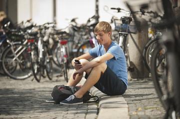Deutschland, München, Karlsplatz, Junger Mann mit Handy in der Universität