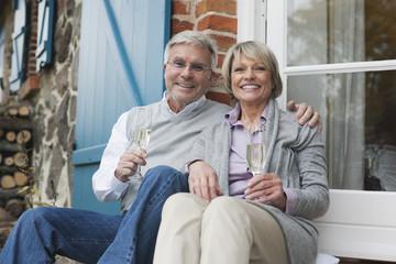 Deutschland, Kratzeburg, älteres Paar, Senioren sitzt auf der Terrasse eines Landhauses mit Champagnerglas