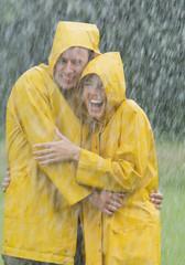 Tragen Paar regen Mantel stehend in regen