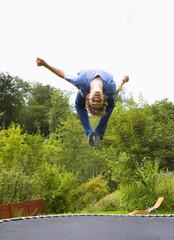 Österreich, Junger Mann springt auf Trampolin