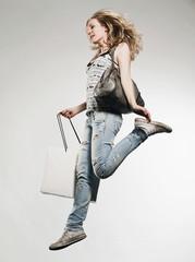 Frau mit Einkaufstüten laufend, grauer Hintergrund