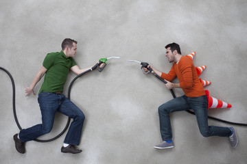 Junge Männer kämpfen gegeneinander mit Tankstutzen