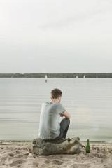 Deutschland, Berlin, Junger Mann sitzt auf Felsen nahe See, Rückansicht