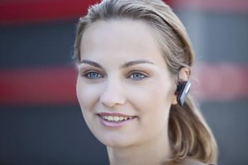 Deutschland, Bayern, Junge Frau mit Headset
