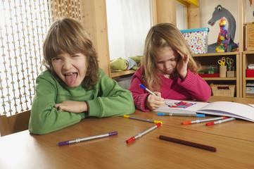 Deutschland, Junge und Mädchen im Kindergarten,Zunge herausstrecken