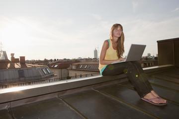 Deutschland, Bayern, München, Junge Frau mit Laptop