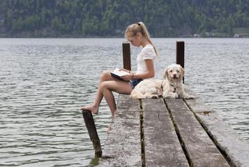 Österreich, Teenager-Mädchen liest ein Buch auf einem Steg, Hund dabei