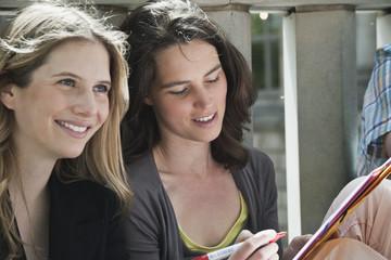 Deutschland, Berlin Zwei Frauen, eine Frau schaut runter und schreibt