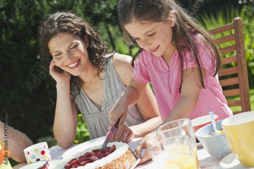 Deutschland, Bayern, Mutter schaut auf Mädchen, schneidet Kuchen