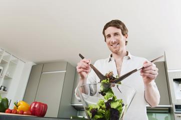 Deutschland, Hamburg, Mann in Küche mit Gemüse