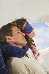 Deutschland, München, Bayern, Paar mittleren Alters trägt Schlafmaske, Schlafen in der Economy-Klasse Verkehrsflugzeug