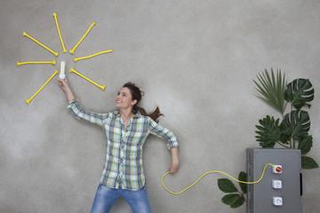 Frau hält eine Glühbirne