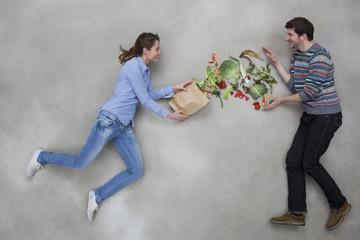 Mann und Frau balancieren Gemüse