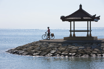 Indonesien, Bali, Sanur, Mann steht mit dem Fahrrad in der Nähe von Pavillon am Meer