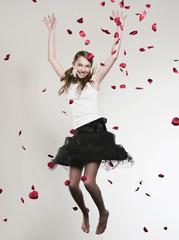 Mädchen mit den Armen oben springend, Rosenblätter fallen