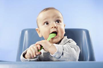 Baby spielt mit Löffel, Wegschauend