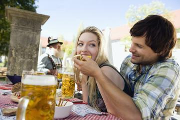 Deutschland, Bayern, Oberbayern, Junger Mann lässt Frau probieren, im Biergarten