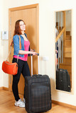 Red-haired positive woman in jeans with luggage leaving the home