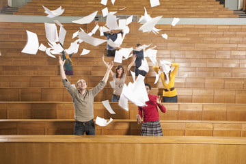Deutschland, Leipzig, Studenten im Hörsaal werfen Papier in die Luft