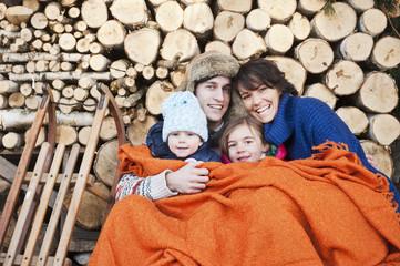 Österreich, Land Salzburg, Flachau, Familie unter Wolldecke sitzt vor firewoods