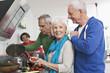 Deutschland, Leipzig, Ältere Männer und Frauen kochen Essen