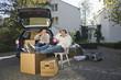 Deutschland, Bayern, Gröbenzell, Paar entspannt auf Stuhl neben Auto