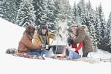 Österreich, Land Salzburg, Flachau, Junge Männer und Frauen sitzen im Schnee am Kamin