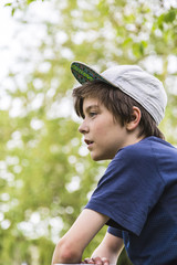 profile of a young boy with basecap and blurred green leafs in b