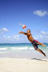 Junger Mann spielt Volleyball am Strand
