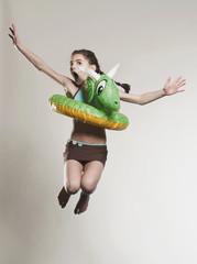 Mädchen springt mit Schwimmreifen