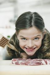 Deutschland, Köln, Mädchen Schneiden von Fleisch mit Fleischklopfer