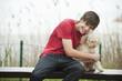 Deutschland, Bayern, Ammersee, Junger Mann und Hund auf der Bank