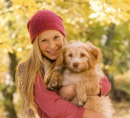 Österreich, Teenager-Mädchen mit Hund im Herbst