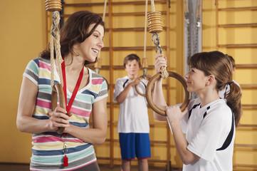 Deutschland, Emmering, Frau und Mädchen mit Gymnastikringen mit Jungen im Hintergrund