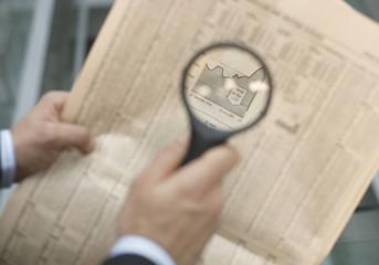 Mann hält eine Lupe über eine Zeitung