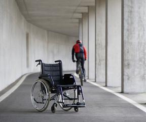 Österreich, Mondsee, Junger Mann auf Mountainbike mit Rollstuhl im Vordergrund
