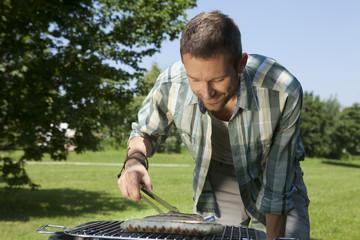 Deutschland, München, Mann bereitet Würstchen auf Grill brabecue