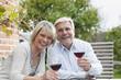 Deutschland, Kratzeburg, älteres Paar, Senioren mit einem Glas Wein sitzen in der Nähe eines Landhauses