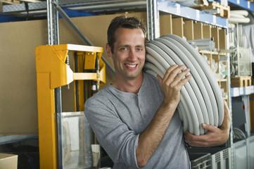Deutschland, Bayern, München, Arbeiter tragen Kunststoffschlauch, Lächeln