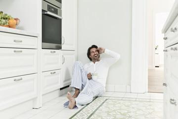 Deutschland, Berlin, erwachsener Mann mit Kaffeetasse in der Küche, Lächeln