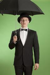 Junger Mann mit Regenschirm vor grünem Hintergrund